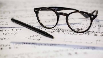 black framed panto-style eyeglasses beside black ballpoint pen